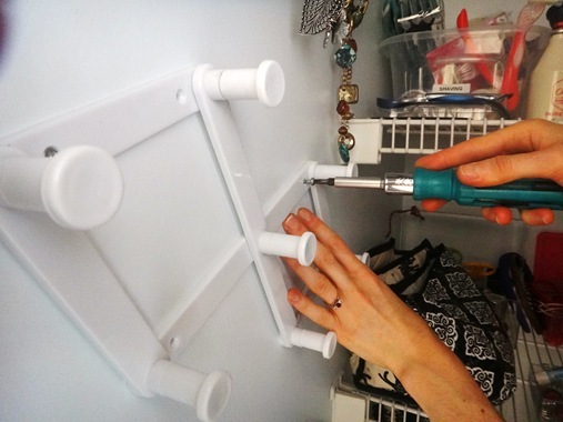 Attaching dollar store hanger to wall with screwdriver