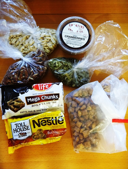 Festively Fall Trail Mix Ingredients- peanuts, pumpkin seeds, pecans, enjoy life chips, butterscotch morsels, puffins, spelt flakes, cranberries