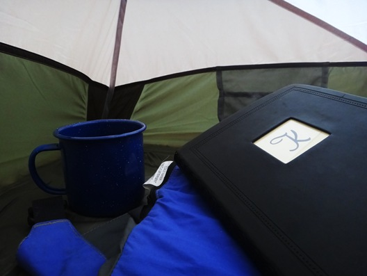 Coffee and journal inside tent